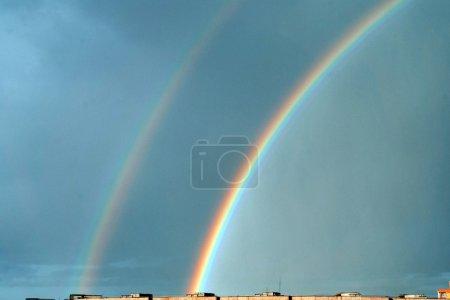 Doppelter Regenbogen über den Dächern der Stadt