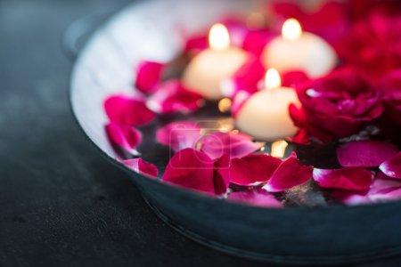 Photo pour Roses rouges avec pétales et bougies dans un bol métallique, fermer - image libre de droit