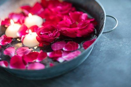Photo pour Pétales de rose rouge et bougies dans l'eau - image libre de droit