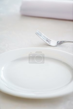 Photo for Empty white plate and fork on table, close-up - Royalty Free Image
