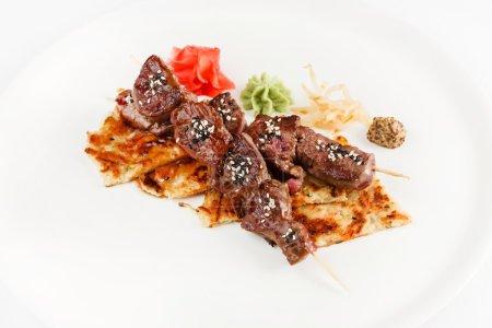 beef on skewers on plate