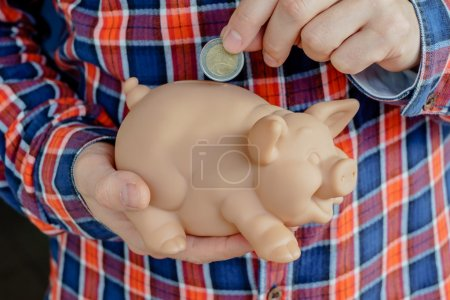 boy holding pig bank