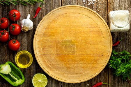 Photo for Vegetables, oil, salt and chopping board on wooden table - Royalty Free Image