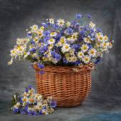 Daisies and cornflowers in a basket on table