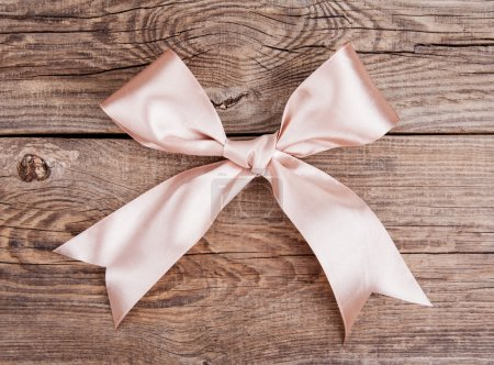 Pink bow lying on the old board