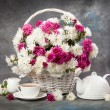 Chrysanthemums in a basket on a wooden table. Stil...