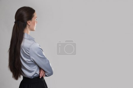 Back view of young business woman looking at copy space