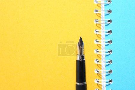 Photo pour Fond de papeterie. Stylo plume sur ordinateur portable avec pages vierges colorées - image libre de droit