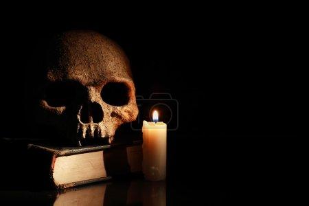Photo pour Un crâne humain sur vieux livre près de bougie d'éclairage sur fond foncé - image libre de droit
