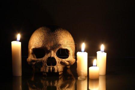 Photo pour Concept de la mort. Un crâne humain près d'allumer des bougies sur fond foncé - image libre de droit
