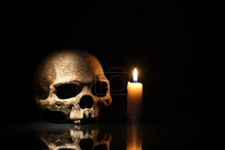 Photo pour Concept de la mort. Un crâne humain près de bougie d'éclairage sur fond foncé - image libre de droit