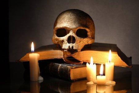 Photo pour Un crâne humain sur vieux livres près d'allumer des bougies sur fond foncé - image libre de droit