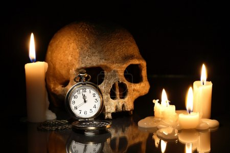 Photo pour Death concept. One human skull and pocket watch near lighting candles on dark background - image libre de droit
