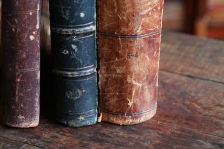 Photo for Closeup of few ancient books in a row on old wooden board - Royalty Free Image