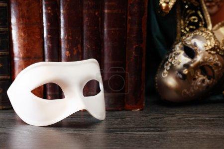Photo pour Concept de théâtre. Gros plan de masque de carnaval classique blanc sur fond de livres - image libre de droit