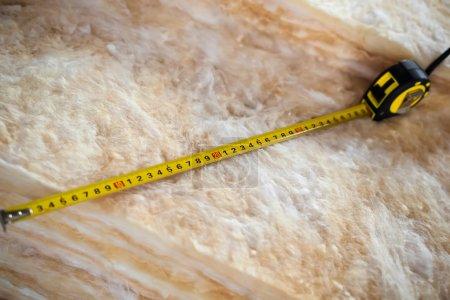 Measure tape on mineral wool
