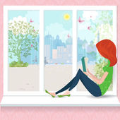 Cute girl is reading a book on a window sill