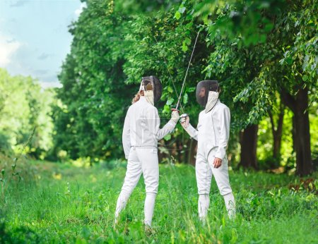 Two fencers women staying in park with crossed rapiers