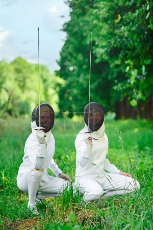Two fencers women squatting down with rapiers pointing up