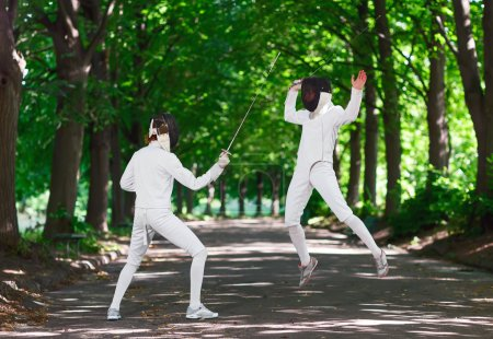 Two rapier fencer women fighting over park alley, attacking each