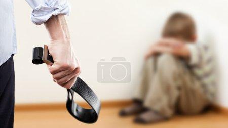 Angry man raised hand holding leather belt over wall corner sitt