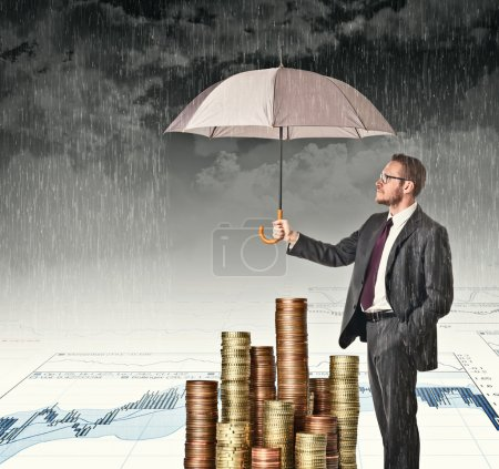 Photo for Businessman cover his money with umbrella - Royalty Free Image
