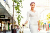 "Постер, картина, фотообои ""Business woman pulling suitcase bag walking in city"""