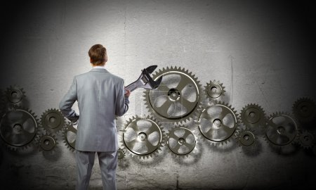 Businessman with wrench in hands and cogwheels