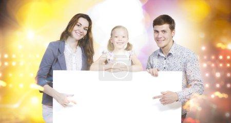 Happy family holding white blank banner