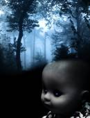 Vintage spooky doll and landscape of foggy forest