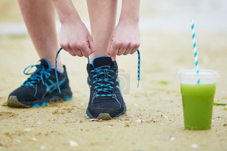 Young jogger with green vegetable smoothie