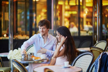 Couple drinking coffee and eating croissants in Parisian cafe