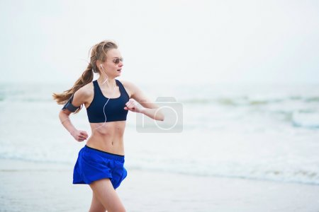 Young fitness running woman jogging on beach