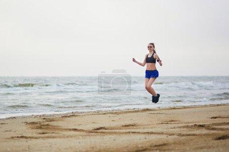 Photo pour Jeune femme fitness jogging rapide sur la plage près de l'océan ou de la mer par une matinée brumeuse brumeuse. Concept de forme physique et mode de vie sain - image libre de droit
