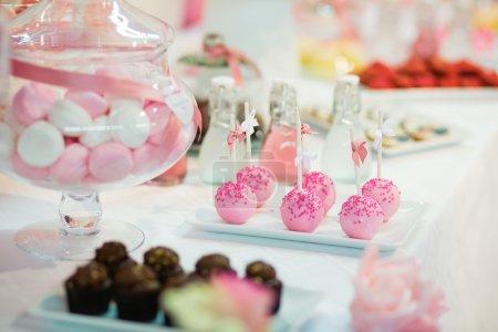 Pink cake pops on a dessert table