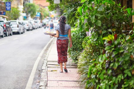 Balinese woman carrying offerings to gods