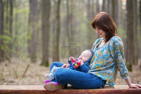 Young mother with her baby boy in forest