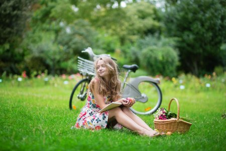 Young girl sitting on the grass and reading a book