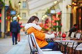 Šťastná dívka pití kávy v pařížské kavárně