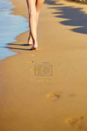 Closeup of legs of a woman on the beach