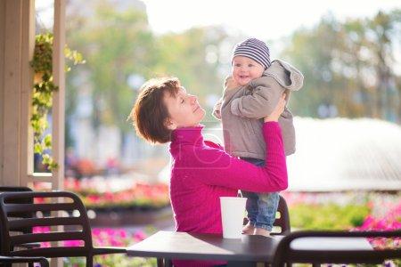 Photo pour Âgées de moyen belle femme et son adorable petit-fils peu s'amuser ensemble dans un café en plein air sur un jour d'automne ou au printemps - image libre de droit