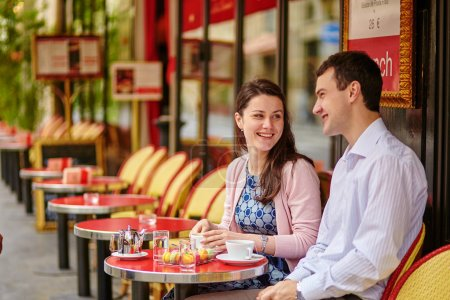 Couple drinking coffee or tea in a Parisian cafe