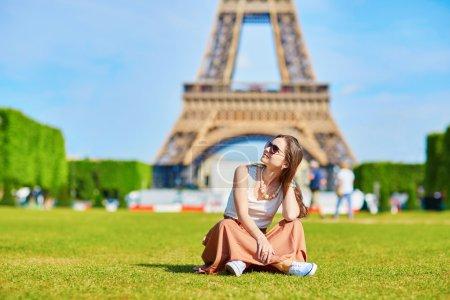 Photo pour Belle jeune touriste ou étudiante à Paris assise sur l'herbe près de la tour Eiffel un jour d'été - image libre de droit
