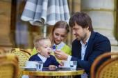 Happy family of three in Parisian cafe