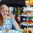 Beautiful young woman enjoying afternoon tea with ...