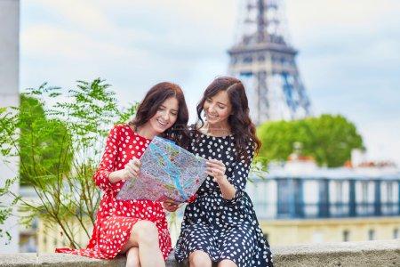 Photo pour Deux soeurs jumelles belle à l'aide de carte en face de la Tour Eiffel lors d'un voyage à Paris. Les filles souriantes heureux profiter de leurs vacances en Europe - image libre de droit