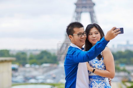Beautiful Asian couple taking selfie in Paris