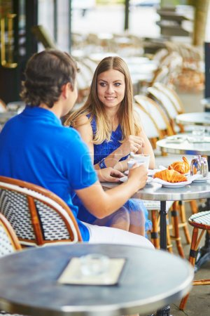 Beautiful young dating couple in Parisian cafe
