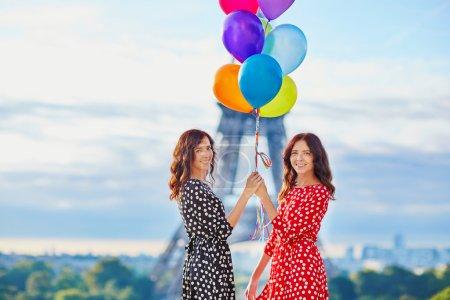 Photo pour Deux sœurs jumelles belle en rouge et noir à pois Robes avec énorme bouquet de ballons colorés en face de la Tour Eiffel à Paris, France - image libre de droit