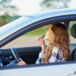 Beautiful blond woman applying lipstick in a car w...